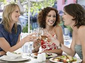 Felices amigas multiétnicas tostado vino en el café al aire libre