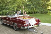 Happy bride and groom waving in retro convertible