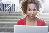 Closeup portrait of a young African American woman with laptop on steps outdoors