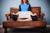 Spiritual Woman Sitting On Sofa Using Her Laptop
