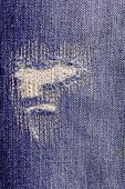 detail of torn blue jeans