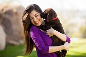 stock photo of licking  - Cute Hispanic woman getting kissed and licked by her brown Labrador - JPG