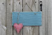 Antique blue sign with red heart and iron keys hanging on wood door