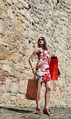 stock photo of cobblestone  - Beautiful young woman in a dress with shopping bags posing on a cobblestoned old city street near a stoned wall - JPG