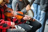 stock photo of banjo  - Close up of street musicians playing banjo and fiddle - JPG