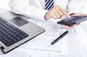 stock photo of economy  - Closeup of hands counting taxes using calculator - JPG