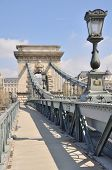The Chain Bridge In Budapest Under A Blue Cloudy Sky