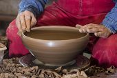 hands of potter do a clay pot