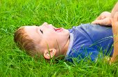 Portrait of cute laughing boy lying on the grass