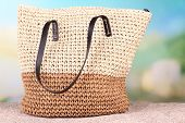 Summer wicker bag on sand, on nature background