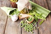 Fresh  and canned peas in bowl and glass jar on napkin, on wooden background