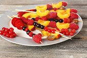Fresh fruit skewers for healthy snack on wooden table close up
