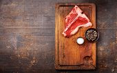 Raw Fresh Meat T-bone Steak With Salt And Pepper On Cutting Board On Dark Wooden Background