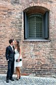 Loving stylish young couple standing in an intimate embrace on a cobbled street outside an old brick