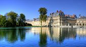 pic of chateau  - View of the Chateau de Fontainebleau and its reflection across a tranquil lake - JPG