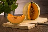 picture of honeydew melon  - Juicy honeydew melon on a wooden table background - JPG