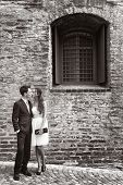 Black and white picture of loving stylish young couple standing in an intimate embrace on a cobbled