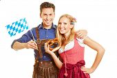 Happy couple in bavaria in traditional outfit with pretzel and flag