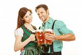 Man and woman drinking beer in Bavaria and clinking their glasses
