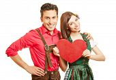 Happy couple in dirndl dress and leather pants with a red heartin Bavaria