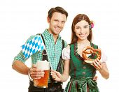 Smiling couple in bavaria to Oktoberfest with beer and pretzel