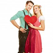 Smiling couple in dirndl and leather pants holding red heart in Bavaria