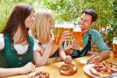Happy friends clinking beer glasses in summer in bavaria