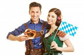 Happy couple in bavaria with dirndl and leather pants holding pretzel and flag