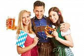 Friends having fun together at Oktoberfest in Bavaria with beer and pretzel