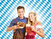 Happy couple smiling with beer at Oktoberfest in Bavaria
