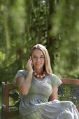 Portrait of beautiful young woman using mobile phone on park bench