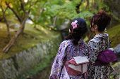 KYOTO, JAPAN, NOVEMBER 16, 2011 : Two Japanese women are enjoying the fall colors in a temple garden