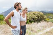 Attractive fit couple standing on mountain trail on a sunny day