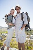 Hiking couple standing on mountain terrain smiling at camera on a sunny day
