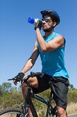Handsome cyclist taking a break on his bike drinking water on a sunny day