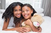 Pretty woman lying on bed with her daughter smiling at camera at home in bedroom