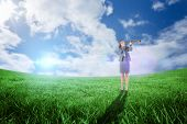 Businesswoman looking through a telescope against green field under blue sky