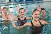stock photo of health center  - Smiling female fitness class doing aqua aerobics in swimming pool at the leisure centre - JPG