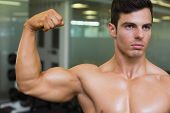 Close-up of muscular man flexing muscles in gym