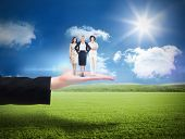 Team of businesswomen looking at camera against sunny green landscape
