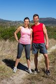 Active couple standing on country terrain smiling at camera on a sunny day