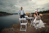 Bride and groom next to  table on the rock