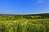 stock photo of bottomless  - Small village lost among the green hills with dense forests covered flowering meadows with the smell of honey and bottomless blue sky - JPG