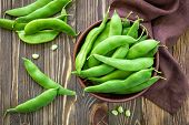 foto of bean-pod  - Green beans in a basket on a wooden table - JPG