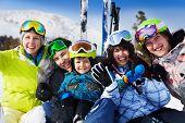 Positive friends with kid together wear ski masks