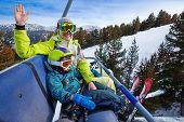 Happy mom and boy in ski masks seat on elevator