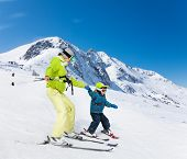 Instructor and kid skiing down the mountain