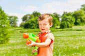 Little boy plays with a water gun