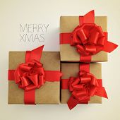 picture of some gifts with a red ribbon bow and the sentence merry xmas on a beige background, with
