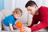 Man And Little Boy Playing With Toys